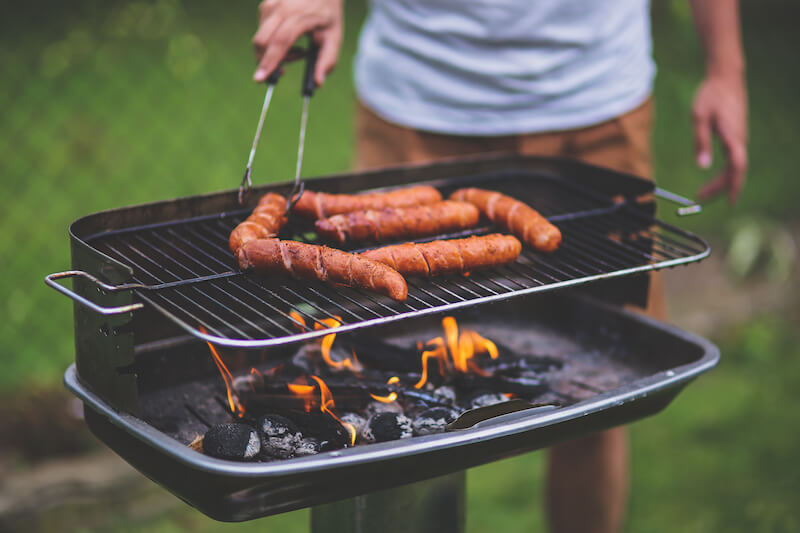 summer safety guide - man grilling hot dogs