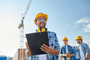 physical capability exams - construction worker holding clipboard on job site